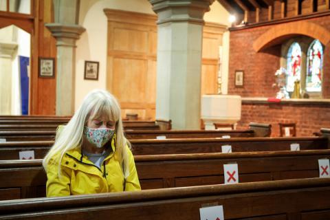 Una mujer en una iglesia con mascarilla.