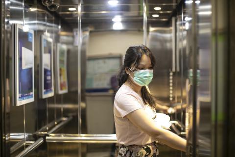 Mujer sube en un ascensor con mascarilla.