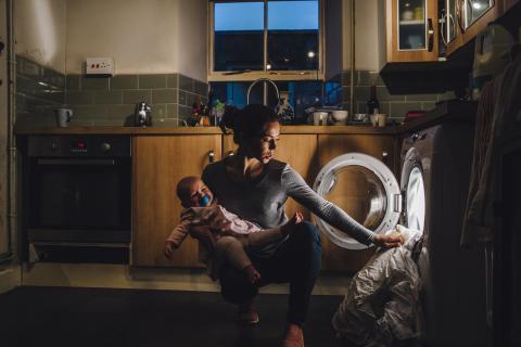Una mujer vacía la lavadora por la noche con un niño en brazos.