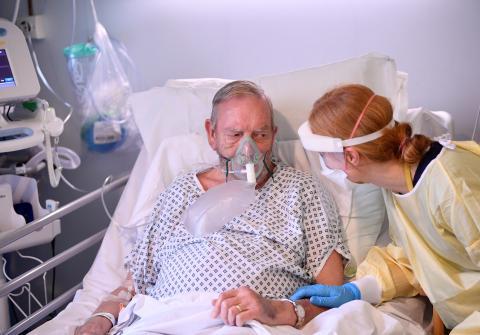 Paciente de COVID-19 es atendido por una profesional de la salud.