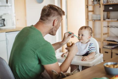 Un padre da de comer a su hijo.