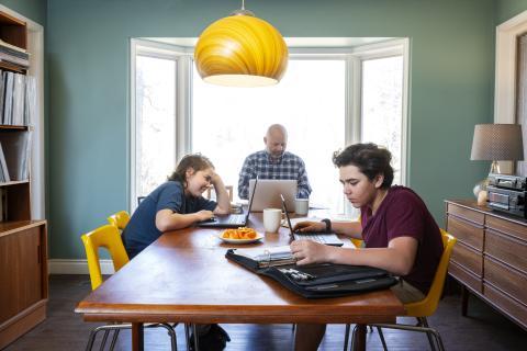 Padre, hija e hijo están en la mesa con un ordenador cada uno.