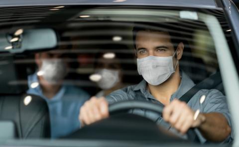 Una persona conduce un coche con un pasajero en la parte de atrás.