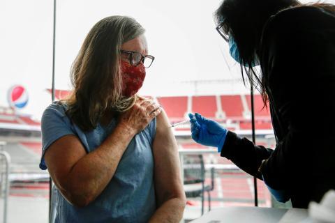 Vacunan a una mujer contra COVID-19.