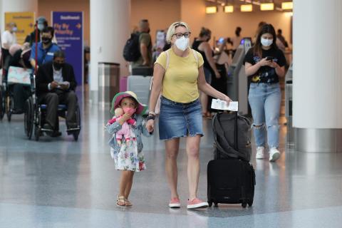 Pasajeros con mascarillas mientras caminan por el Aeropuerto Internacional de Los Ángeles.