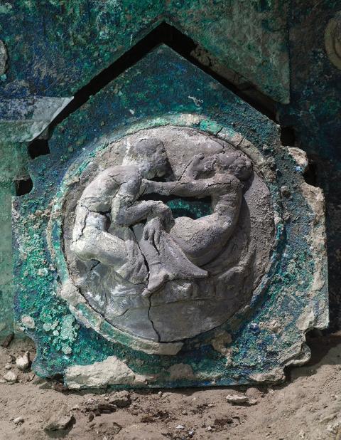 Un detalle de la decoración de un carro, con sus elementos de hierro, adornos de bronce y restos de madera mineralizada.