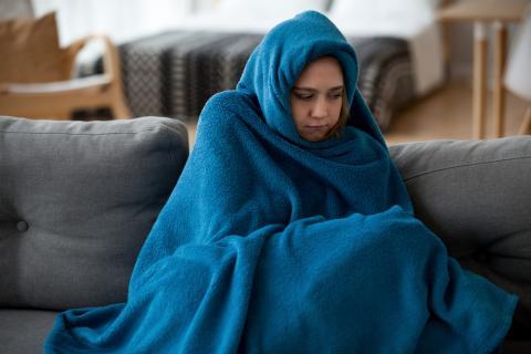 Chica con una manta en el sofá.