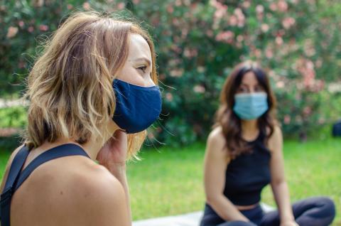 Chicas hablando en un parque con mascarillas.