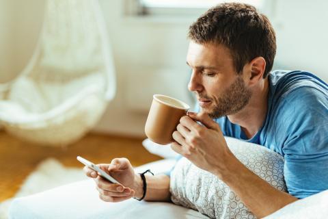 Un chico toma café mientras mira el móvil.