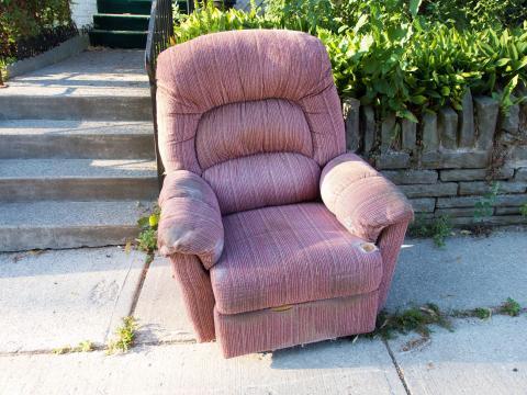Un sillón viejo abandonado en la acera.