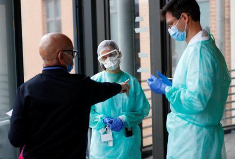 Dos médicos escuchan a un paciente de un hospital psiquiátrico durante el confinamiento