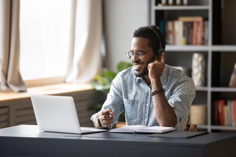 Un hombre con auriculares delante del ordenador.