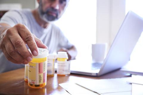 Hombre con botes de pastillas.