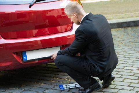 Hombre cambiando la matrícula de su coche