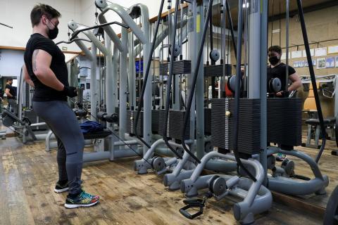 Un hombre hace ejercicio en el gimnasio con mascarilla para protegerse del coronavirus.