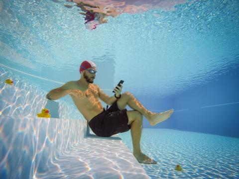 Hombre con el movil en una piscina