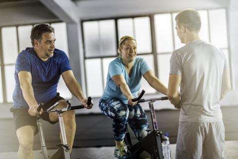 Un hombre y una mujer atienden al profesor en una clase de spinning
