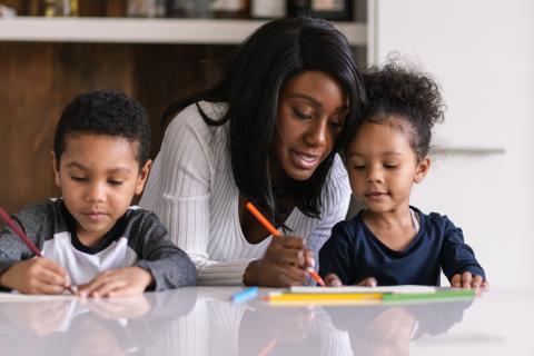 Una madre hace los deberes de su hija.