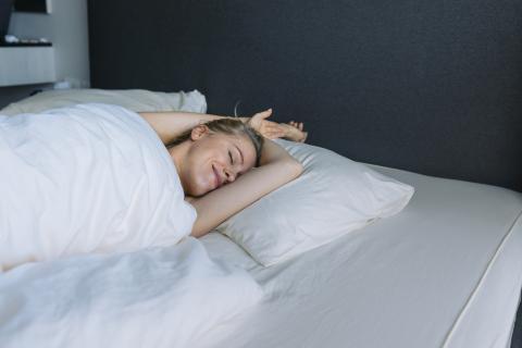 mujer en la cama, beneficios de dormir desnudo