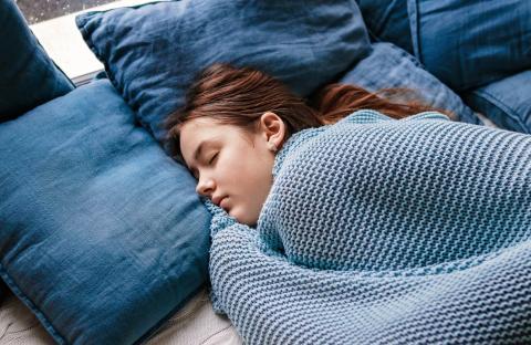 Mujer durmiendo con una manta.