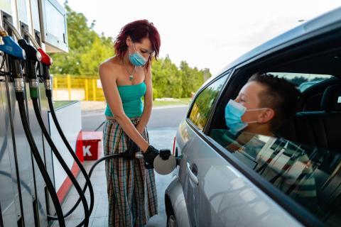 Una mujer echa gasolina, mientras su hijo mira por la ventanilla del coche.