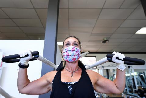 Mujer haciendo pesas con mascarilla y guantes en un gimnasio.