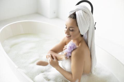 Mujer lavándose con una esponja de baño.