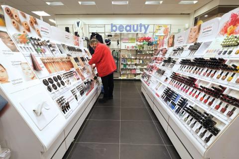 Una mujer limpia los estantes de maquillaje de una tienda