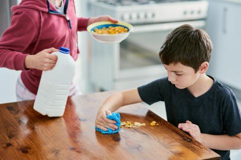 Un niño limpia la mesa de la cocina