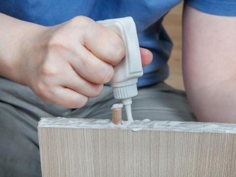 Una persona aplica pegamento para madera a un mueble.