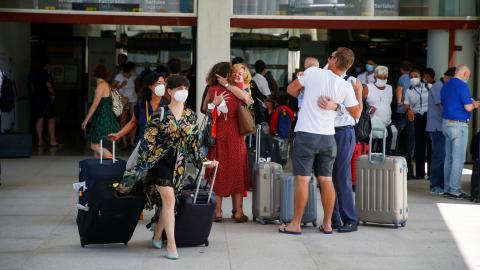 Personas reencontrándose en las puertas de un aeropuerto.
