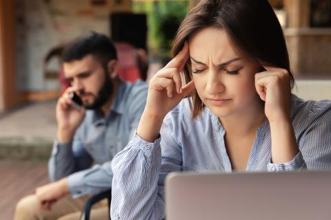 En primer plano una mujer intenta concentrarse, mientras un hombre habla por teléfono detrás.