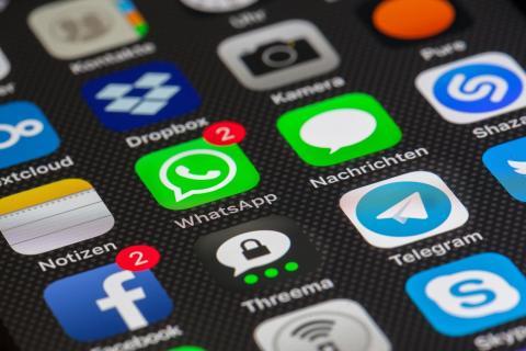Un teléfono con dos notificaciones de WhatsApp y otras dos de Facebook.