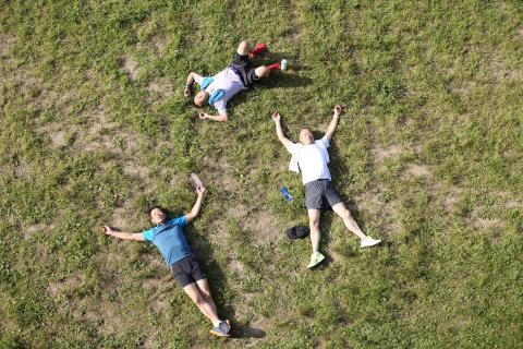 Tres hombres descansan tirados en el suelo