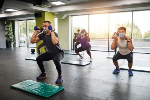 Varias personas hacen sentadillas con peso en el gimnasio.