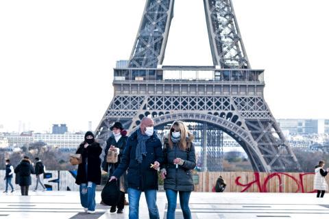 Varias personas pasean por el entorno de la Torre Eiffel en París
