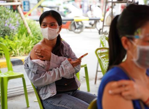 Una chica espera tras recibir la vacuna contra el COVID-19.