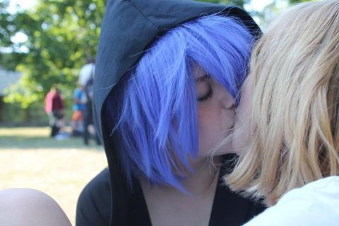 Dos mujeres se besan inclinando la cabeza hacia la derecha.