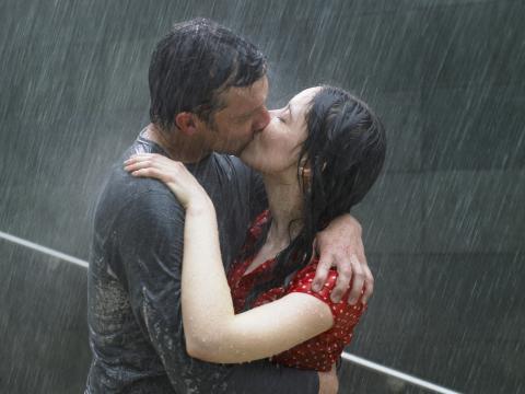Dos personas se besan bajo la lluvia.