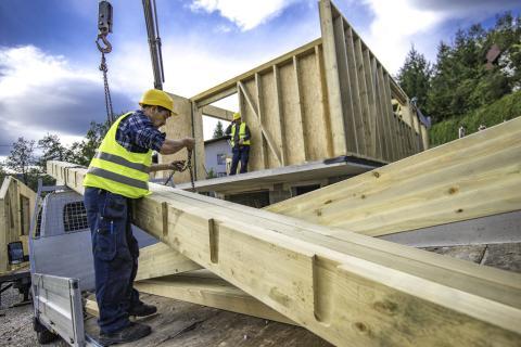 Dos personas fabrican una casa de madera.