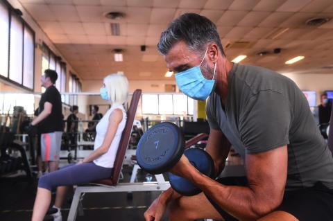 Un hombre hace ejercicio en un gimnasio con una mascarilla puesta.