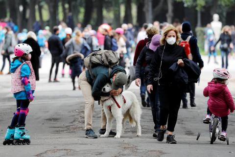 Un hombre abraza un perro en la calle en medio de la pandemia.
