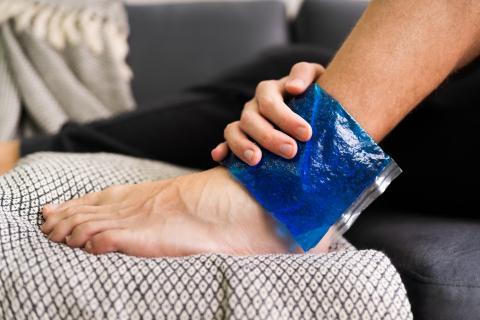 Un hombre con la pierna hinchada se pone una bolsa de hielo.