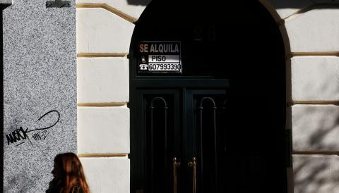 Una joven pasa ante un portal con un anuncio de piso en alquiler en Madrid