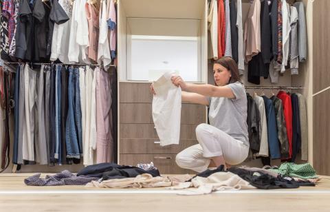 Una mujer joven ordena la ropa de su armario