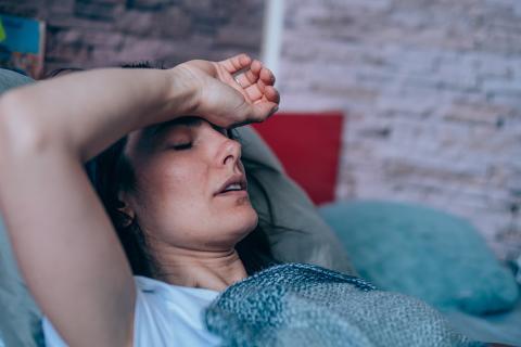 Mujer con mareos en la cama.