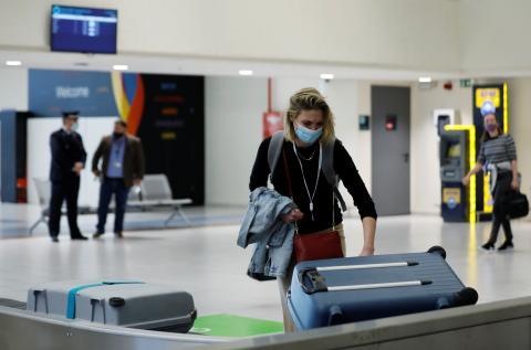Una mujer recoge una maleta en la cinta del aeropuerto.