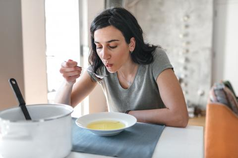 Una mujer toma sopa.