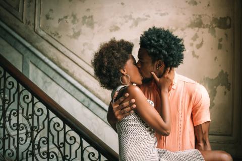 Una pareja se besa al pie de unas escaleras.