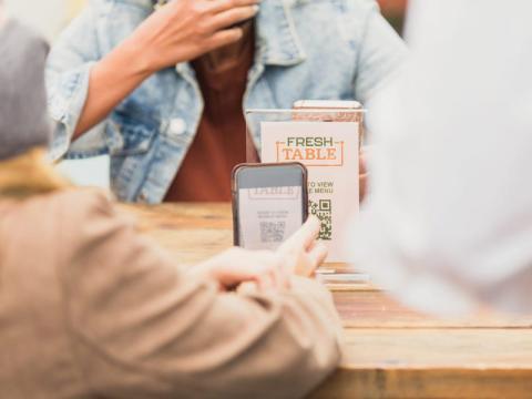 Una persona lee un código QR en un restaurante.